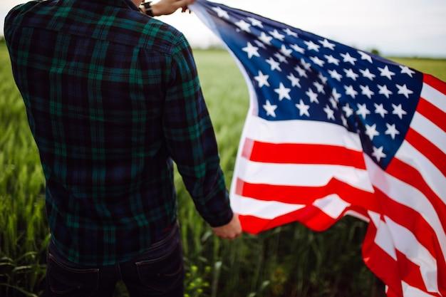 День независимости. мужчина в клетчатой рубашке с американским флагом в поле.
