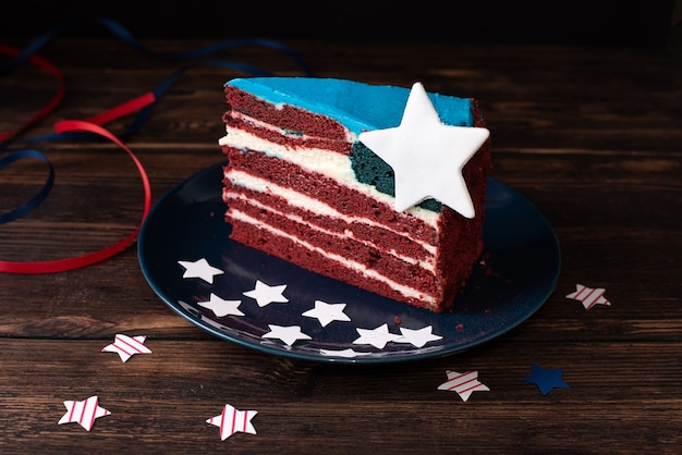 Independence day celebration, piece of cake in the colors of the usa flag on a dark wooden background, 4th of july concept, close up.