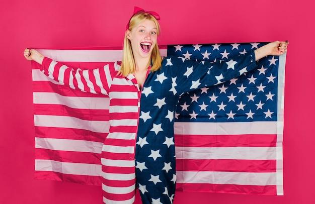 Празднование дня независимости. улыбающаяся девушка с американским флагом в руке. национальные цвета сша.