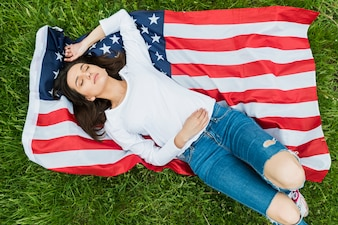 Independence day concept with lying woman and american flag