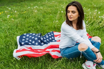 Independence day concept with sitting woman and american flag