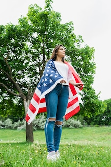 Independence day concept with woman and american flag in front of tree