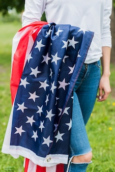 Independence day concept with woman carrying american flag