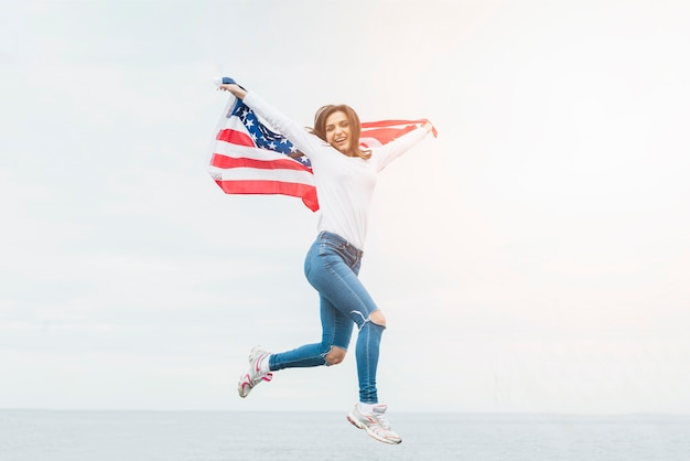 Independence day concept with woman holding flag on sky background