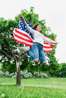 Independence day concept with woman jumping with american flag