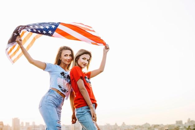 Концепция дня независимости с молодыми девушками на крыше