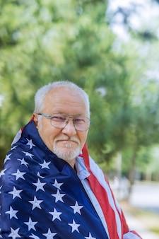 幸せな年配の男性の独立記念日ポジティブな笑顔は、米国連邦の休日のアメリカの旗の愛国者をカバーします