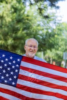 幸せなシニア愛国者の独立記念日は、米国連邦の休日の大きなアメリカの国旗に星条旗を掲げています