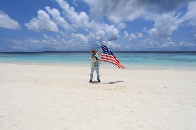 アメリカの独立記念日熱帯の島の海岸にアメリカ国旗を持った男