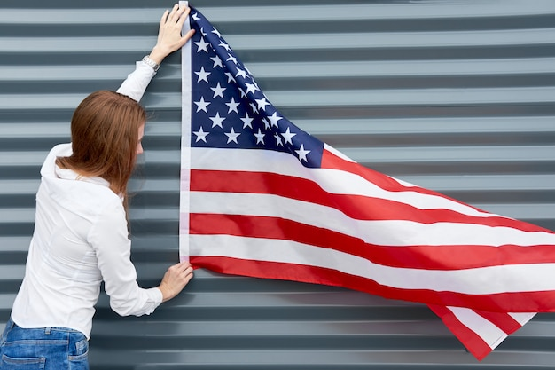 Independence day and patriotic concept. young redhead woman with red painted lips standing with waved by wind usa flag, holding it above. grey metal panel background.