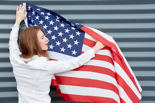 Independence day and patriotic concept. young redhead woman with red painted lips standing with waved by wind usa flag