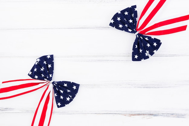 Independence day patriotic flag bows on white wooden surface