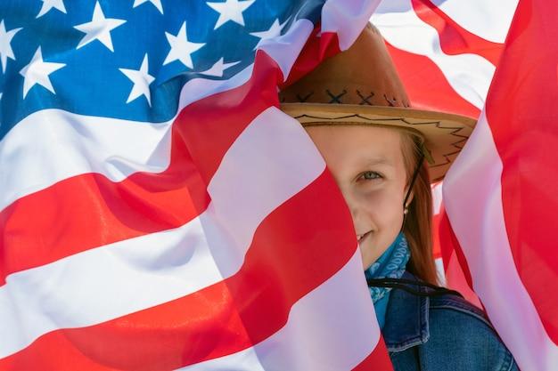 独立記念日。愛国的な休日。明るい晴れた日にアメリカの国旗の背景に緑色の目を持つ美しい幸せな女の子。カウボーイハットとデニムジャケットの女の子。