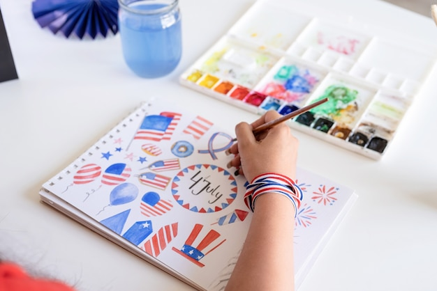 Independence day of the usa. happy july 4th. beautiful woman drawing a watercolor illustration for independence day of the usa