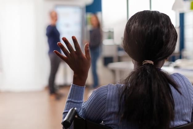 독립 장애를 가진 아프리카 여성 기업가가 휠체어 인사팀에 움직이지 않고 앉아 손을 흔들며 창업 사무실에 들어오고, 다양한 동료들이 창업 금융 회사를 환영합니다.