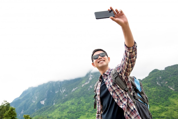 Independent asian tourist man taking selfie with natural green mountain scenery