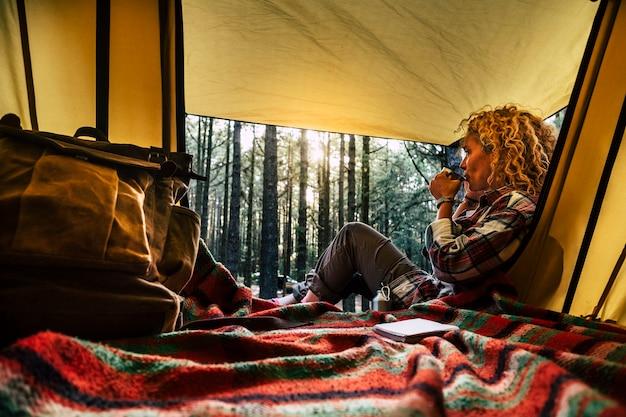 独立した美しい巻き毛のブロンドの髪の女性は、森の中で無料の野生のキャンプでテントの外に座ってお茶を楽しみ、考えています-屋外の自然なライフスタイルと別の旅行方法