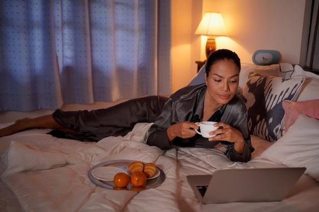ノートパソコンで作業し、白いシーツでコーヒーを飲む独立した美しい少女。若い女性はブログ記事を書き、白いステンレス鋼のプレートに朝食のコーヒーとクロワッサンを食べました。