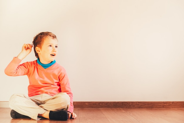 Independent child of 5 years combing himself sitting on the floor of his house