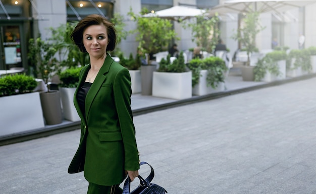 Independent lady walking down the street, holding her purse. fashionable green jacket on her. short and sexy haircut, confident and smart
