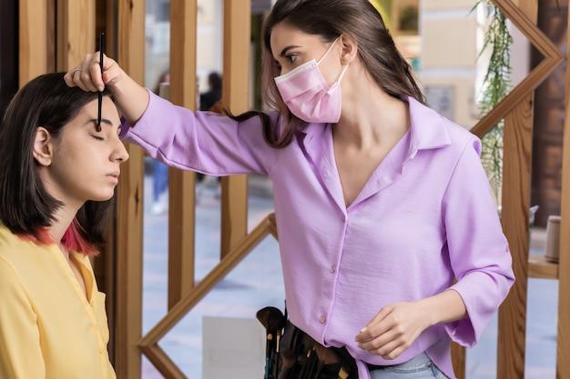 Covid19ライフスタイル中小企業の肌の専門家のための医療マスクで保護された若いヒスパニック系女性に化粧品を適用する独立したメイクアップアーティスト黄色とラベンダーの年の色