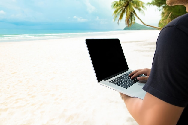 Independent man working with laptop computer online at the beach