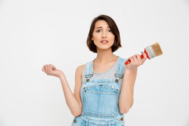 Самостоятельная женщина сама занимается ремонтом дома, держит малярную кисть