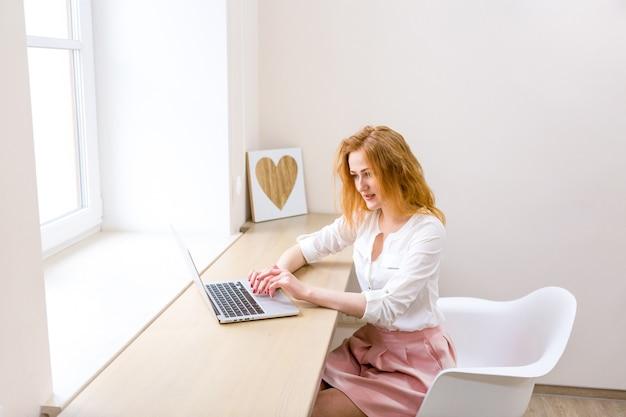 Независимый женский портрет. молодой предприниматель с рыжими волосами и веснушками, работающими на серебряном ноутбуке, вводит клавиатуру, сидя у окна в офисе. кавказская женщина-работник консалтинг-клиент онлайн