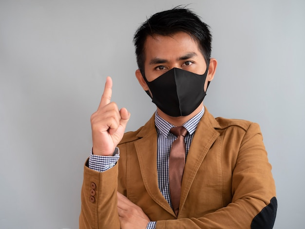 The index finger of a male hand is pointing up and wear mask trying to protect from coronavirus