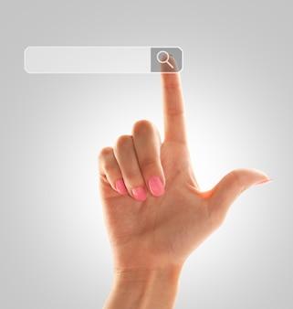 女性の手の人差し指が検索フィールドを指す