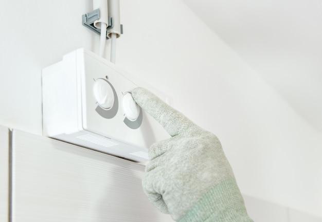 Указательный палец на кнопке регулировки датчика влажности.