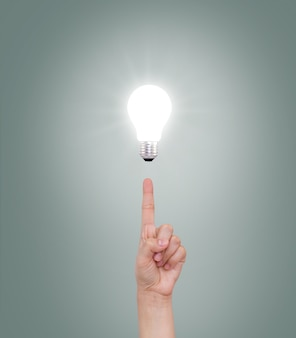 Index finger pointing at an illuminated bulb