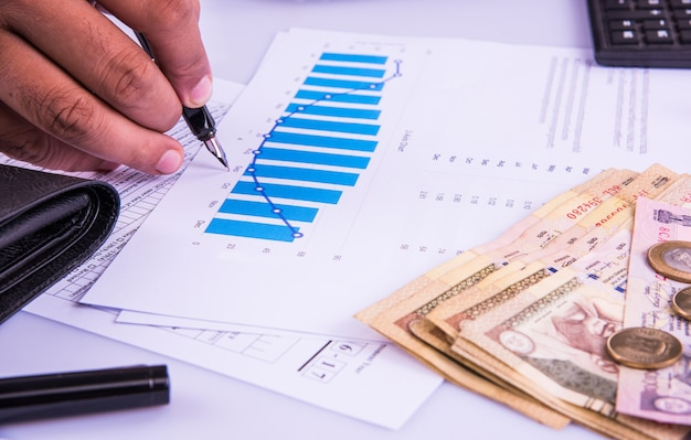 India and accounting concept showing accountant working on income tax forms or on budget planning with currency notes, calculator and house or car 3d models