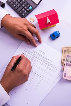 India and accounting concept showing accountant working on income tax forms with currency notes, calculator and house and car 3d models