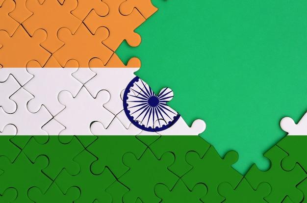 인도 국기는 오른쪽에 무료 녹색 복사 공간이있는 완성 된 직소 퍼즐에 그려져 있습니다.