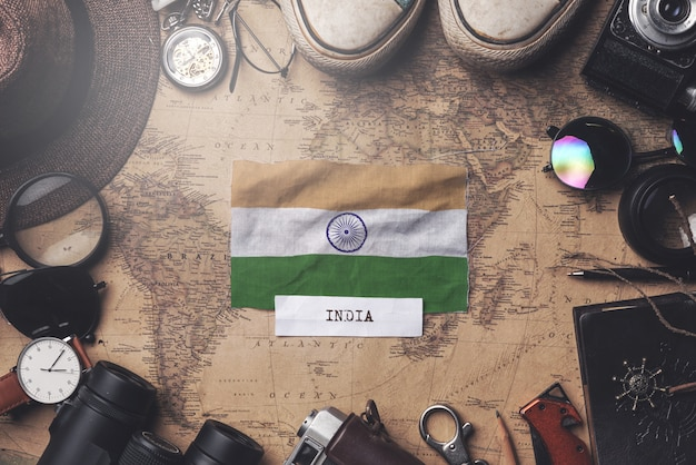 India flag between traveler's accessories on old vintage map. overhead shot