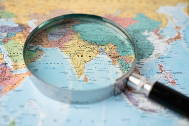 India, magnifying glass close up with colorful world map.