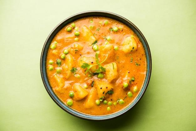 Indian aloo mutterカレー-ジャガイモとエンドウ豆をオニオントマトのグレービーソースに浸し、コリアンダーの葉を添えて。カラヒまたはカダイまたは鍋またはボウルでお召し上がりいただけます