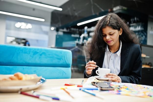 Индийская женщина-художник носит официальную картину краски и пьет чай, сидя в кафе.