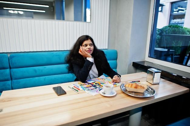 Индийская женщина-художник носит официальное изображение краски и слушает индуистскую музыку в наушниках, сидя в кафе.