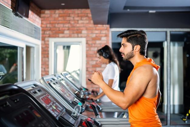 건강 및 피트니스 개념-피트니스 센터 또는 체육관, 선택적 focys에서 심장 훈련 프로그램을하고 인도 아시아 매력적인 부부