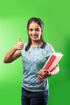 Индийская азиатская привлекательная студентка держит книги на зеленом фоне классной доски с рисунками, выборочный фокус