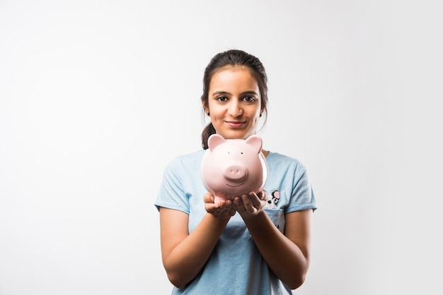 Indian asian attractive female student with holding piggy bank over green chalkboard background with doodles, selective focus