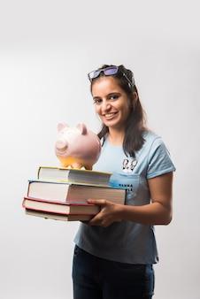 녹색 칠판 배경 위에 돼지 저금통을 들고 있는 인도 아시아 매력적인 여학생