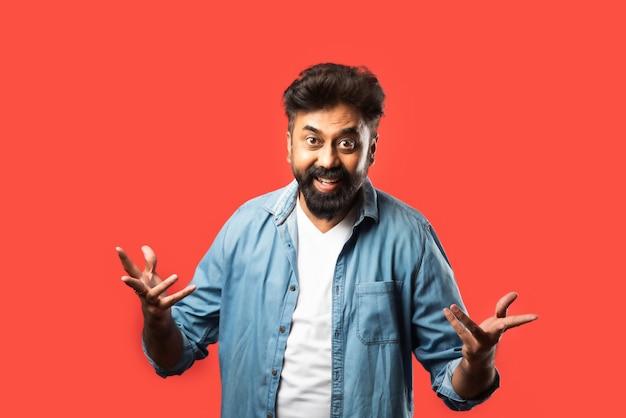Индийский азиатский бородатый мужчина с удивленными или вау-взглядами, стоящий на красном