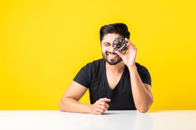 수염을 기른 인도 아시아 청년은 노란색 또는 흰색 배경에 대해 식탁에 앉아 있는 동안 도넛이나 도넛을 먹는다