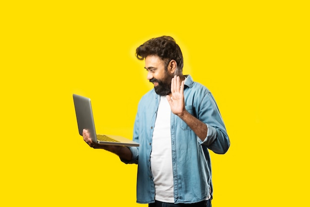 노란색에 서있는 동안 노트북을 사용하는 캐주얼 옷에 인도 아시아 수염 젊은 남자