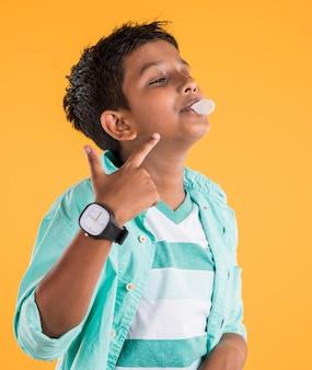 Indian or asian boy blowing balloon out of chewing gum or bubble gum, isolated over yellow background