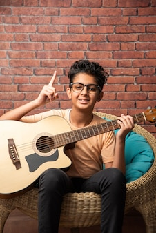 Indian asian boy playing acoustic  guitar while sitting against white wall