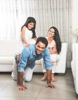 Индийская азиатская дочь сидит на спине отца и едет, а мать смотрит